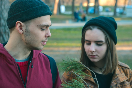 beg: two happy homeless man and woman hold pine stick in the evening Stock Photo