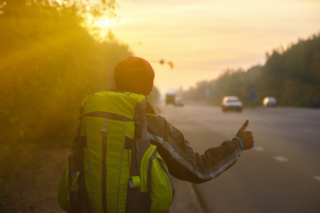 jailbreak: Hitchhiking young traveller try to catch car in the morning Stock Photo