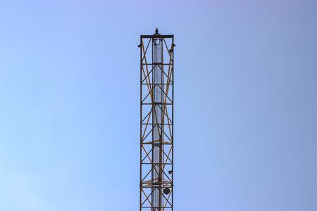 hoists: Building crane and building under construction against blue sky