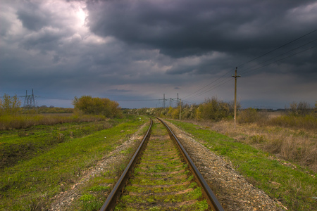 railroad near high voltage power lines at stormy sunset with dramatic sky Фото со стока
