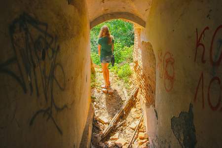 red-haired girl in handcuffs in an abandoned building