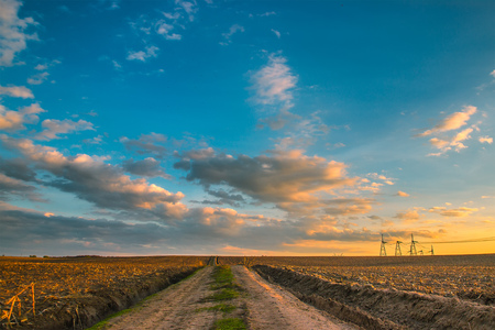 power cables: Beautiful landscape of meadow with road and high voltage power line Stock Photo