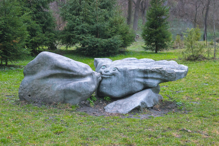 Sculptural group of stone idols kissing on the grass Stock Photo
