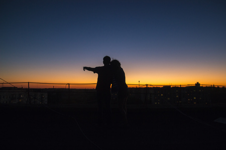 Silhouette couple playing scenario towards the sunset at roof Stock Photo