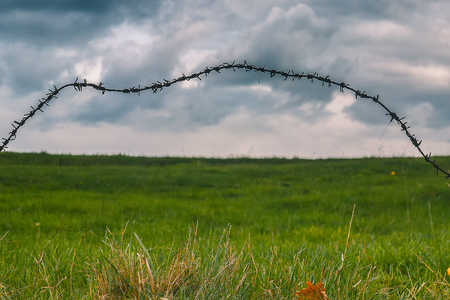 Barbed wire trembling in the wind on the dark stormy clouds time lapse