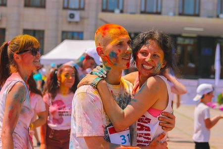 personas festejando: Zhytomyr, Ukraine - June 25, 2016: happy people crowd partying under colorful powder cloud at holi fest, festival of colors in summer, amazing moment, then run competition