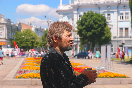 Zhytomyr, Ukraine - June 25, 2016: beggar with sigarette partying among colorful powder cloud at holi fest, festival of colors in summer, amazing moment, then run competition