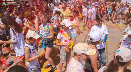 Zhytomyr, Ukraine - June 25, 2016: happy people crowd partying under colorful powder cloud at holi fest, festival of colors in summer, amazing moment, then run competition