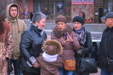 Zhytomyr, Ukraine - October 28, 2015: Mother proves something to her friends at phone