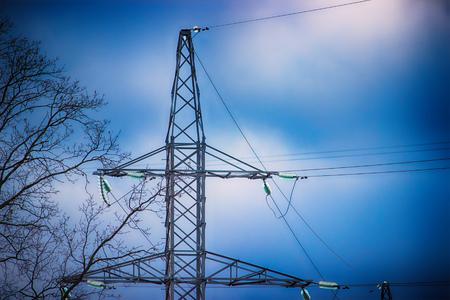 electricity transmission pylon closeup with dark blue sky