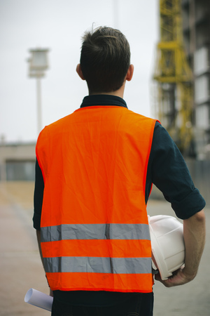 Construction engineer or worker or construction foreman holding safety white helmet and Blueprint standing in construction site.