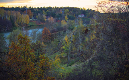 Wood village houses near hill with autumn trees and river