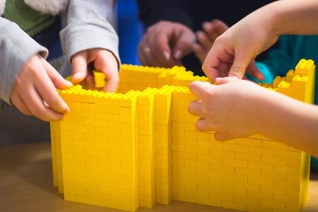 Children playing with construction at orange blocks