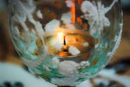 burning candle on the table, green background
