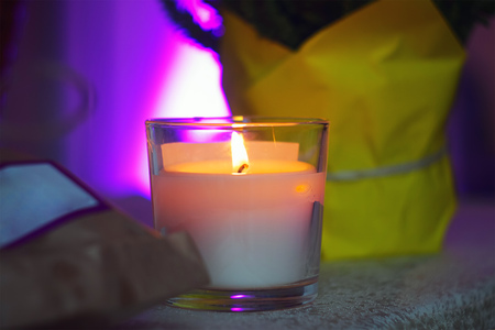 burning candle on the table, purple background 스톡 콘텐츠