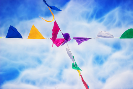 crossed multicolored flags against the blue cloudy sky 免版税图像
