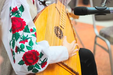 Woman playing music with balalaika. Lifestyle concept. Russian instrument. Folk music russian ensemble - woman playing the balalaika Stock Photo