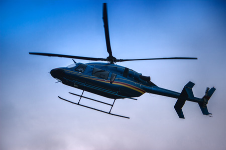 Helicopter fly at the blue evening sky