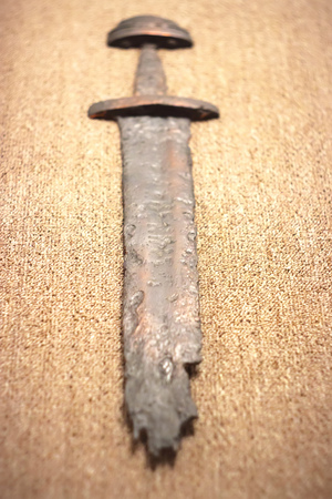 War symbol. Medieval viking rusty sword on linen cloth. Selective focus 스톡 콘텐츠