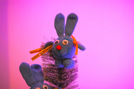 toy rabbit on the tree at purple background