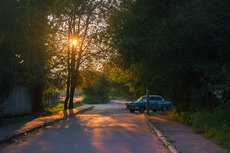 vintage car on the road among the green trees of the summer day