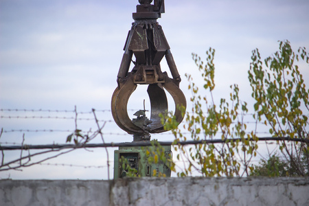 a large industrial crane with rust on the background of a gray sky above the fence Stock fotó