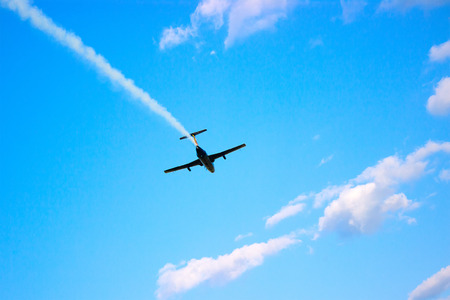 blue plane flying against a blue sky with white clouds