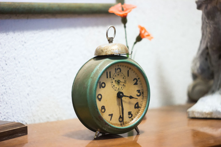 Vintage rusty metal analog alarm clock with numbers and wind-up mechanism, sitting on a wooden bench with retro background.