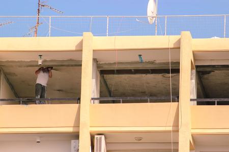 a worker in a white cloak digs the floor Foto de archivo