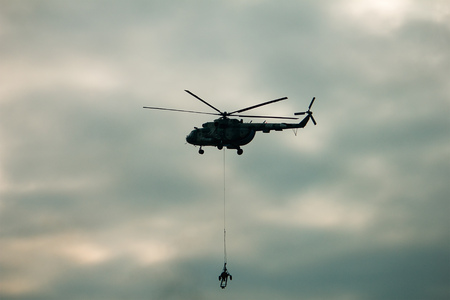 military army helicopter transporting an artillery piece at evening Imagens