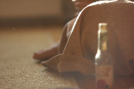 Beautiful girl in a brown linen medieval dress sitting on the floor 免版税图像