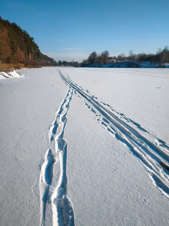 Human traces and animals in the snow at frozen river 写真素材