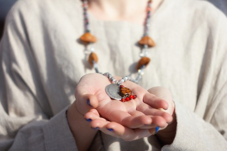 Concentrated woman praying holding rosary beads. Close up
