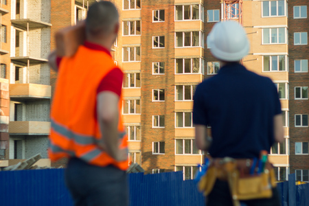 Two engineer builders with blueprint plan. Man in vest pointing at construction site. Back view