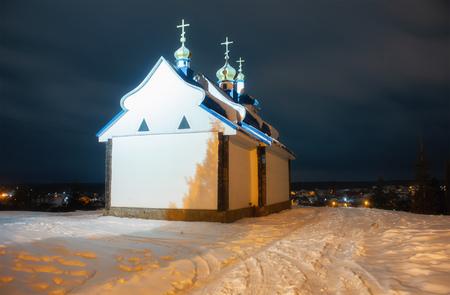 Orthodox church in winter at dark blue night sky