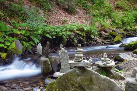 Balanced Rock Zen Stack in the front of waterfall. 写真素材