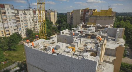 Aerial Building Process of the Construction Site. Engineers crane and city.