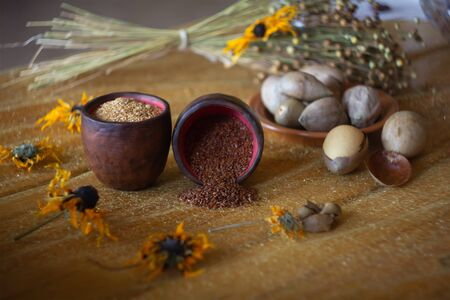 Composition of flax, sesame and avocado seeds in banks at yellow flowers background
