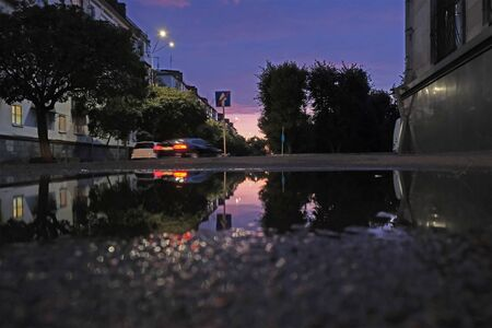 Low shot of puddle whilst it rains with city traffic 写真素材