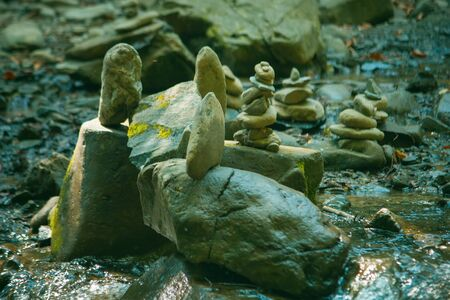 A lot of stones in balance with the river background 写真素材