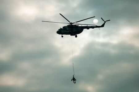 Three military army helicopters transporting an artillery piece at evening