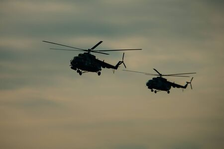 Helicopter in the flight at sunset above war field