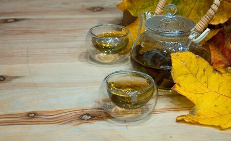 Autumn glass cup of tea and fallen maple leaves Stock Photo