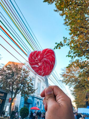 Sweet candies on a stick in the shape of a red heart in the hands in the evening. The concept of love and friendship. Valentines day concept. Romantic background. Selective focus. Stock Photo