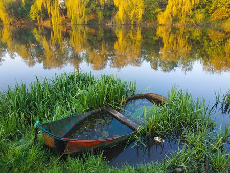 small drowned boat near river in the shore Stock Photo