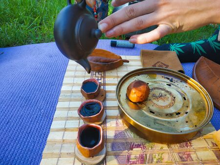 Tea ceremony at the park. Pouring tea at bowls Stock Photo