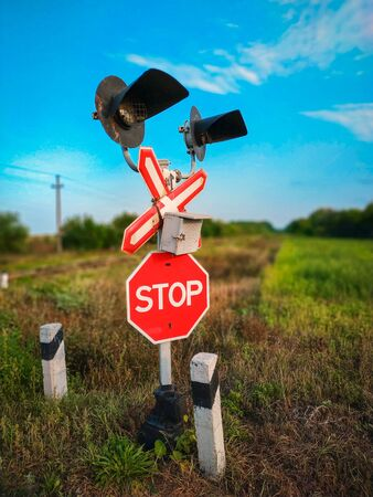 Railroad crossing with warning stop sign and lights in the countryside Stock Photo