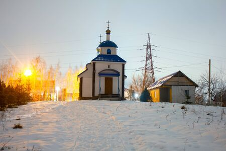 Night city church on light background. Old town. Scenic cityscape. Outdoor tourism landscape at winter snow.