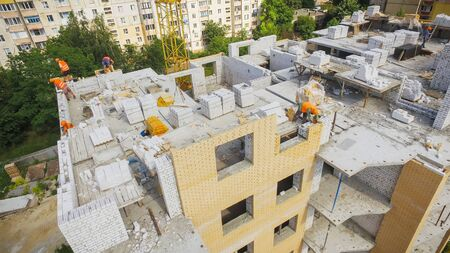 Aerial View of Building Process at the Construction Site. Engineers crane and city suburbs.