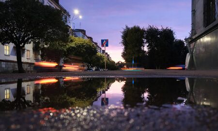 Low shot of puddle whilst it rains with city traffic Stock Photo